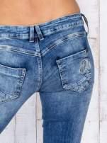 Niebieskie jeansowe spodnie rurki z przetarciami i haftami                                  zdj.                                  5