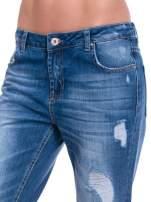 Niebieskie spodnie girlfriend jeans z poszarpaną na dole nogawką                                  zdj.                                  6
