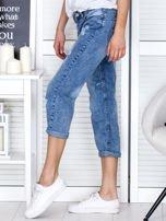 Niebieskie spodnie jeansowe z dekatyzacją i przedarciami                                  zdj.                                  3