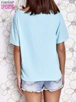Turkusowy t-shirt z różowymi pomponikami przy dekolcie                                  zdj.                                  4